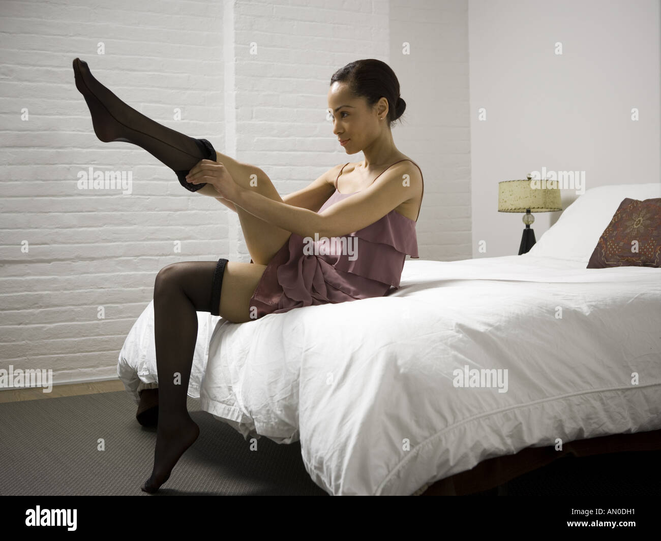 665ce3f32455c Portrait of a young woman putting on stockings Stock Photo: 8783312 ...