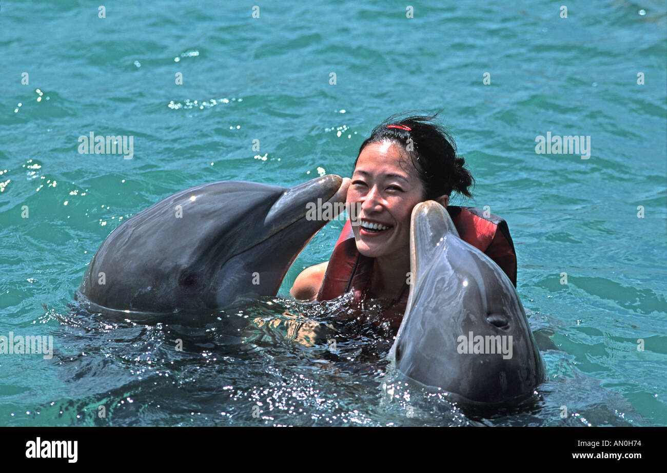 Woman swimming with dolphins Guadarlavaca Holguin province Cuba - Stock Image