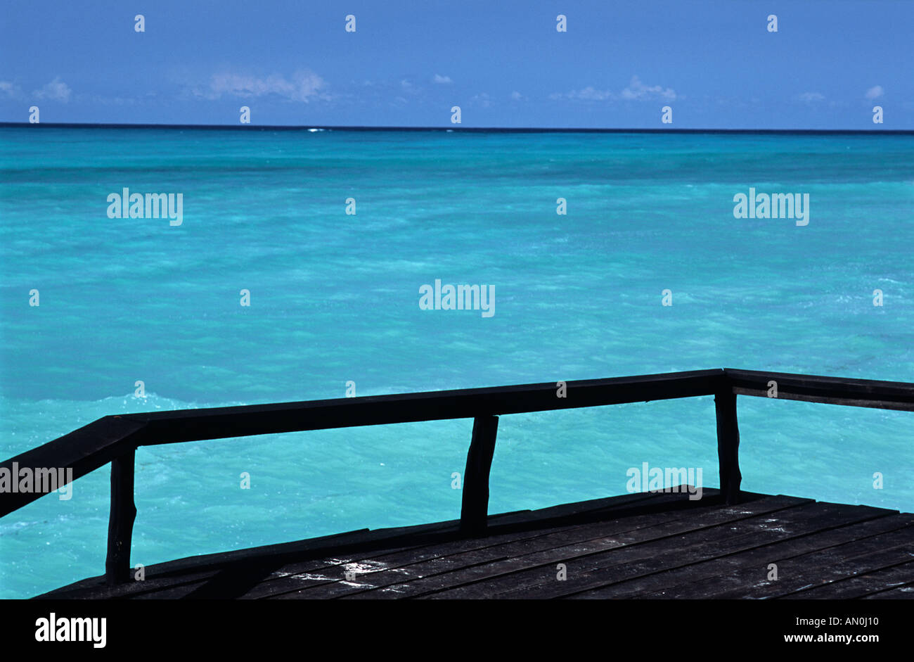 Silhouetted wooden terrace overlooking the turquoise waters off the coast of northern Unguja at Nungwi Zanzibar Tanzania - Stock Image