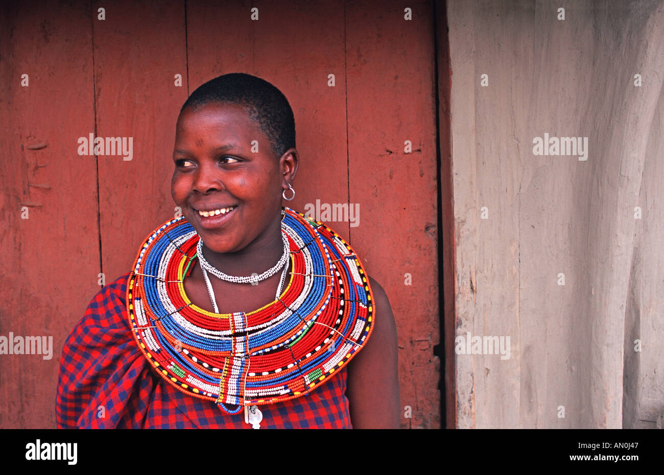 Masai woman in tribal dress outside her home village N of Arusha near to cattle market en route to S Kenya Tanzania - Stock Image