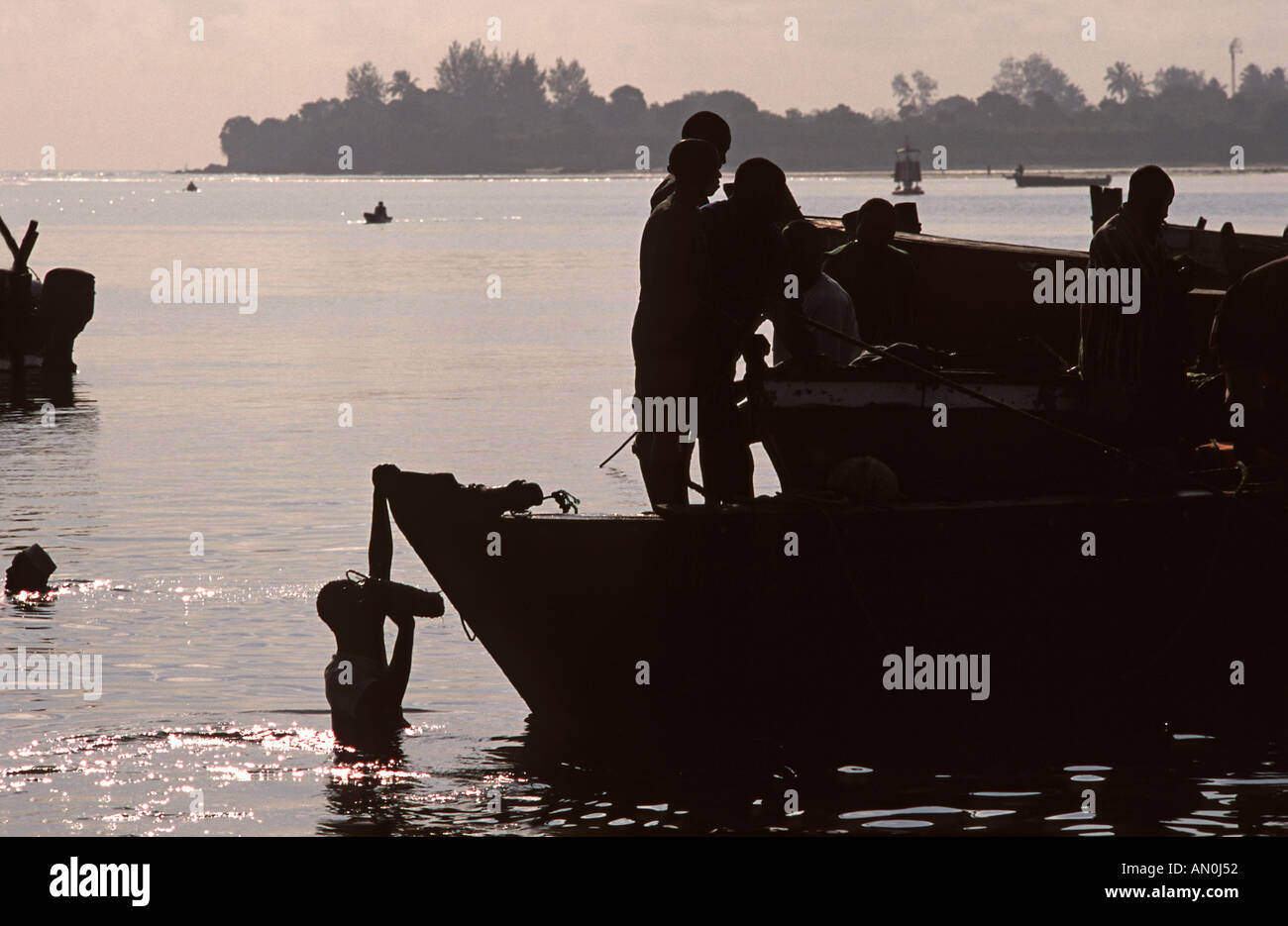 Silhouetted shapes Boat moored beside the fish market passing fish from boat to bucket to shore Dar es Salaam Tanzania - Stock Image