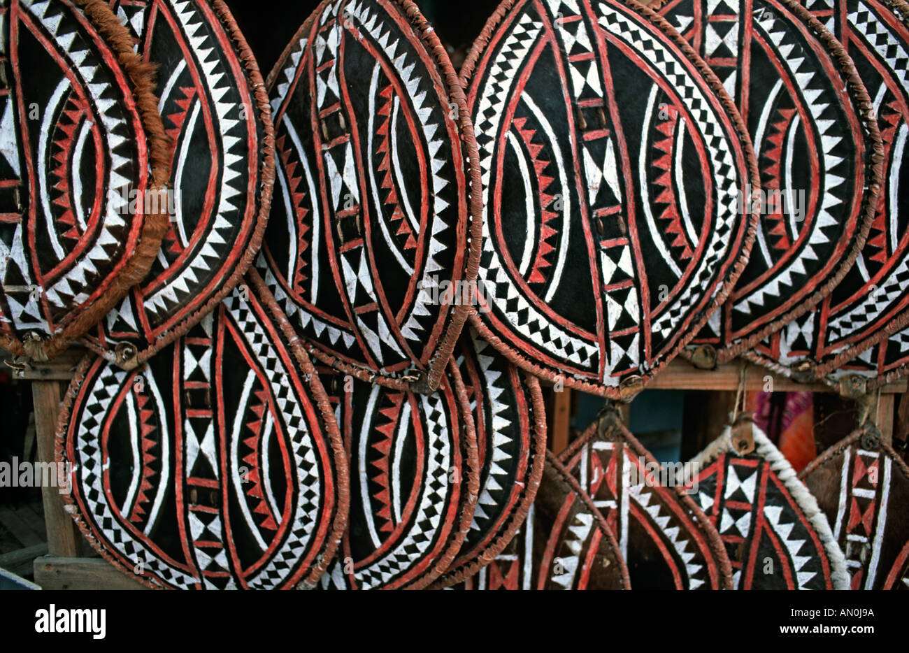Selection of Masai shields made from hide and painted with geometric motifs sold as souvenirs on a market stall Tanzania - Stock Image
