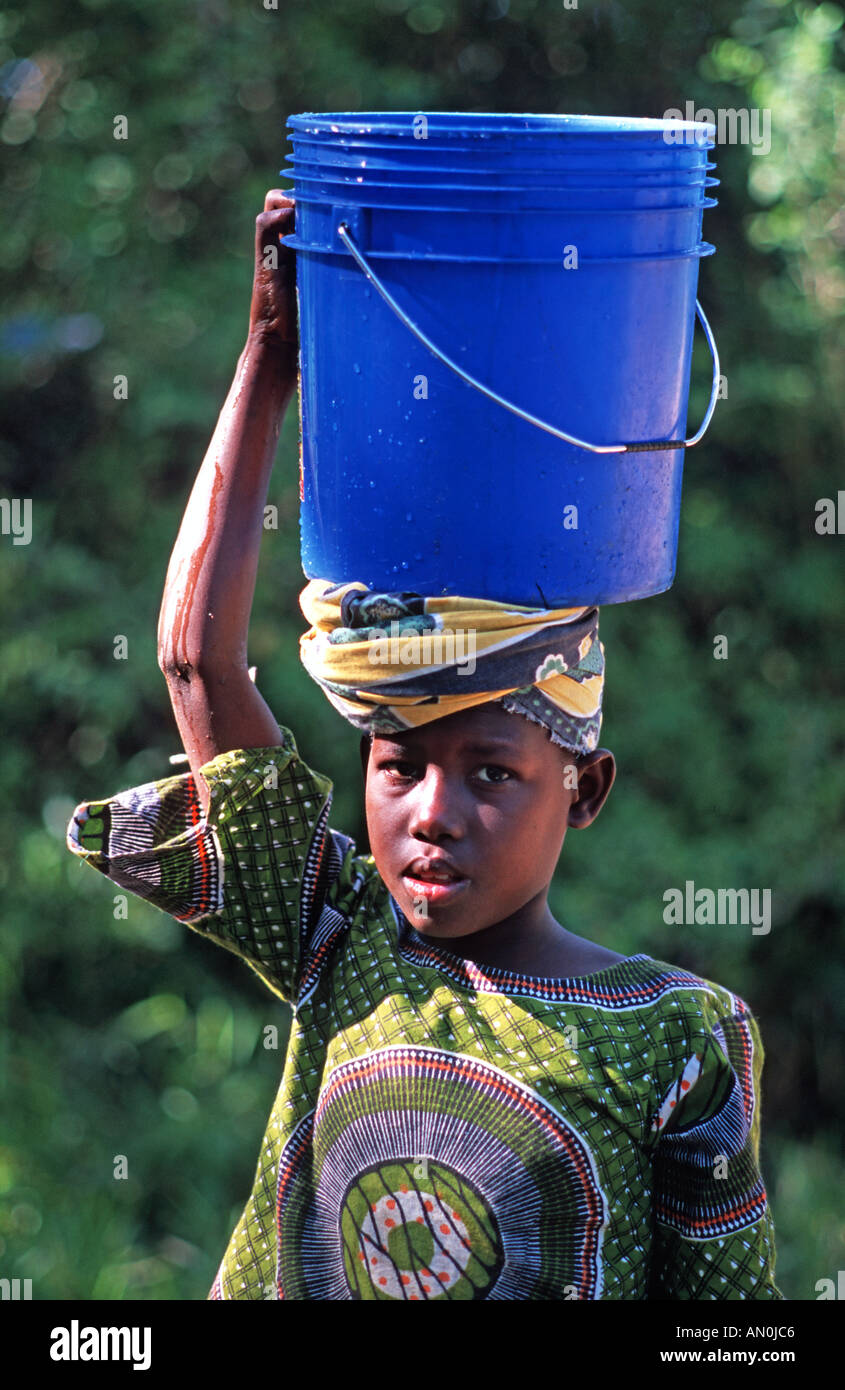 Girl from Utende with a water bucket balanced on her head Mafia island Mafia lies between Zanzibar and northern Mozambique - Stock Image