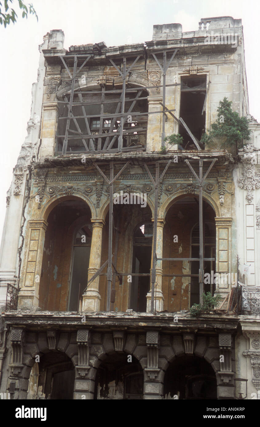 Ancient building on the point of collapse in Havana, Cuba, being supported by wooden supports. - Stock Image