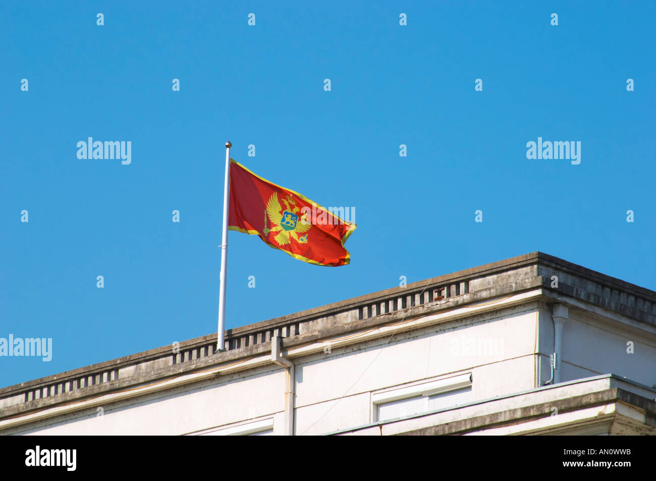 The Montenegrin flag flying on top of a building, red with a golden double headed eagle. Podgorica capital. Montenegro, Stock Photo