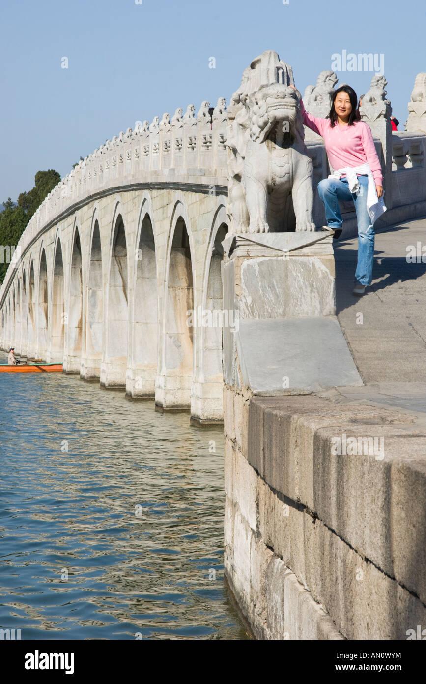 China Beijing The Summer Palace Kunming Lake Seventeen Arch Bridge young woman pausing at bridge - Stock Image
