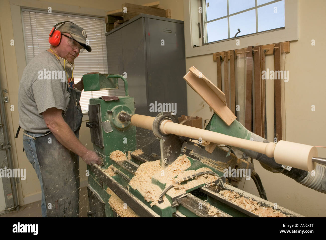 Worker turns a billet of ash wood on a lathe to make a baseball bat at Cooperstown Bat Company - Stock Image