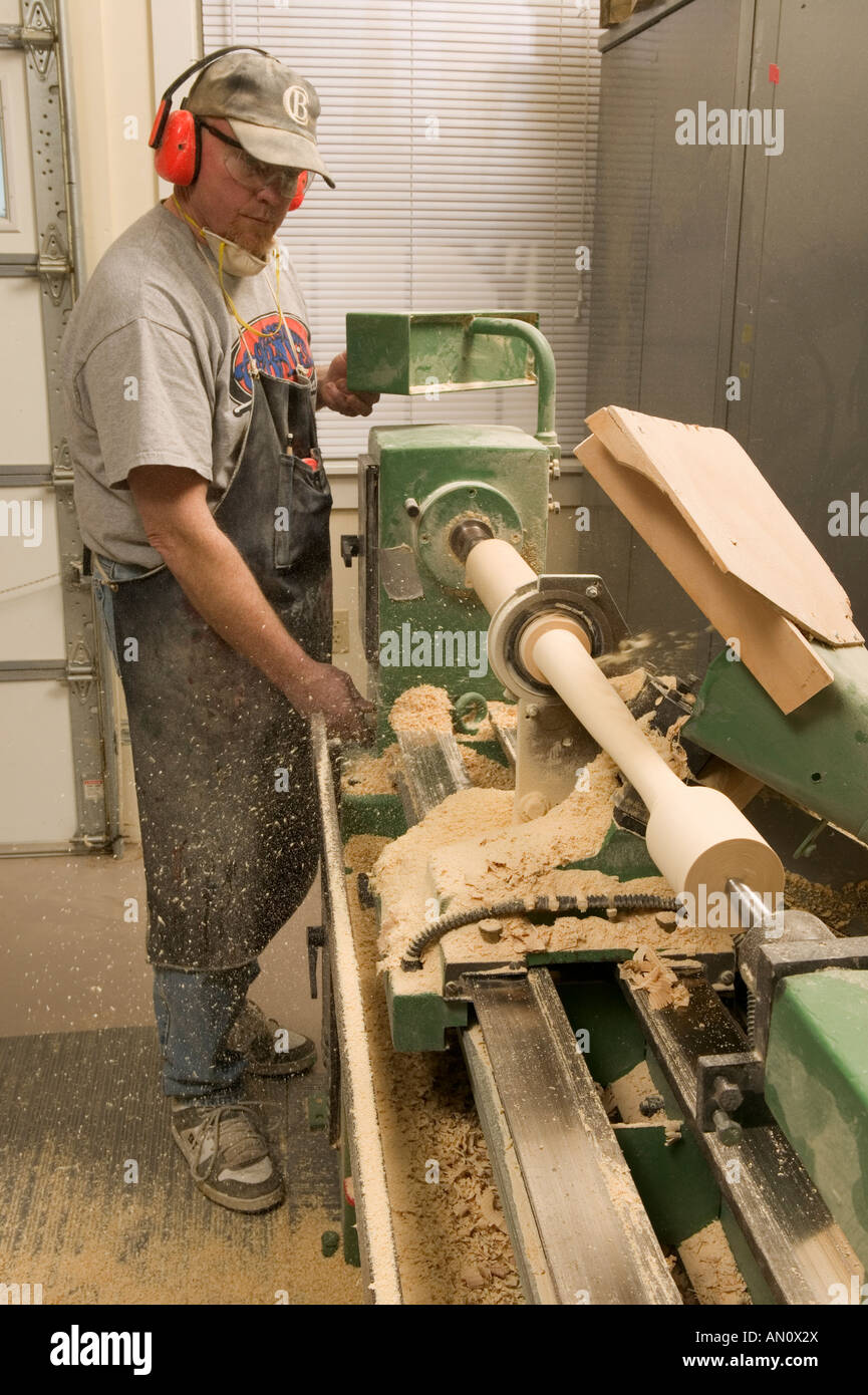 A worker turns an ash billet on a lathe to make a baseball bat in Cooperstown New York - Stock Image