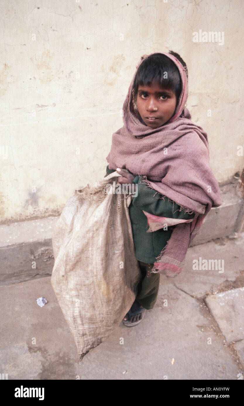 Young boy at work carrying sack. India - Stock Image