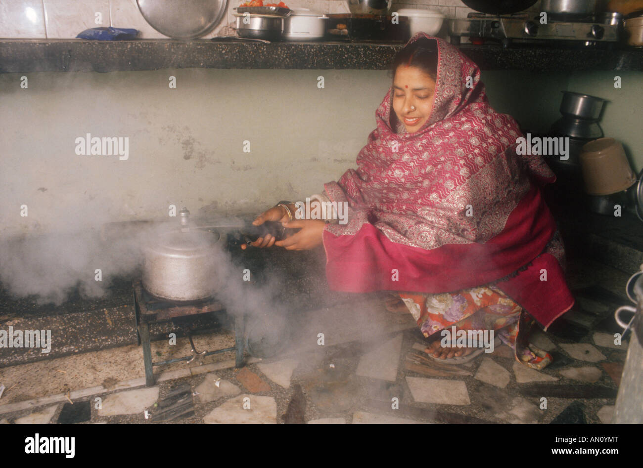 Kitchen of middle-class family in Gobindigarh, Punjab, India, with mother cooking with pressure cooker. - Stock Image