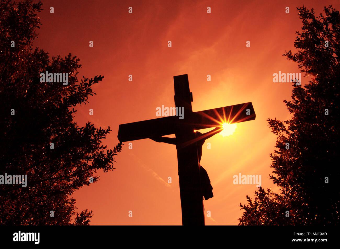 Statue of Jesus Christ on Cross at Sunset - Stock Image