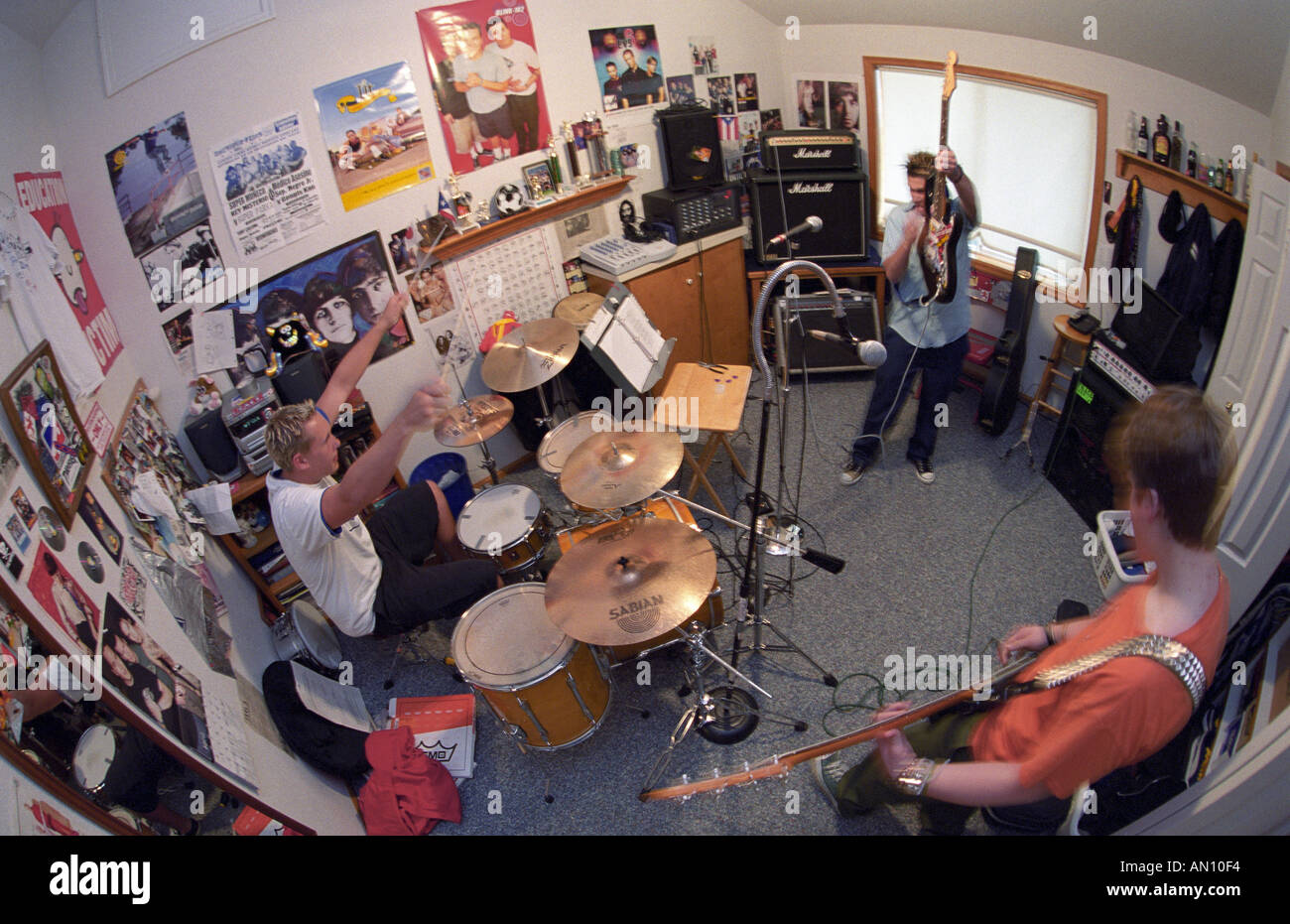 High school punk rock band 36drive practices in bedroom - Stock Image