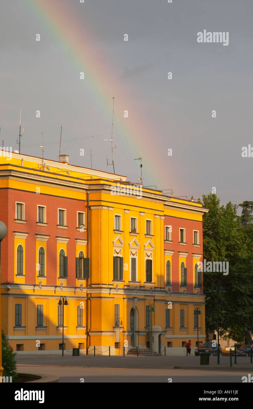 National administrative buildings in bright yellow and red in classic architecture style around the square. A rainbow in the sk - Stock Image