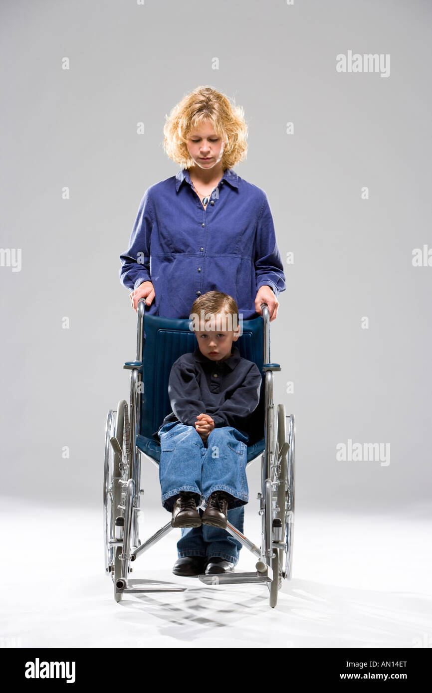 Mother with child in wheelchair - Stock Image