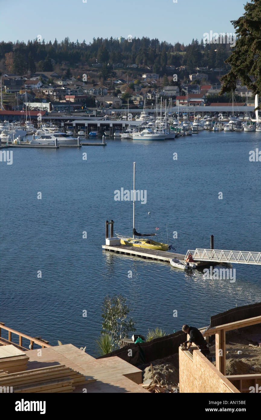 Man building new waterfront home with harbor view from East Shore across bay to town of Gig Harbor WA - Stock Image