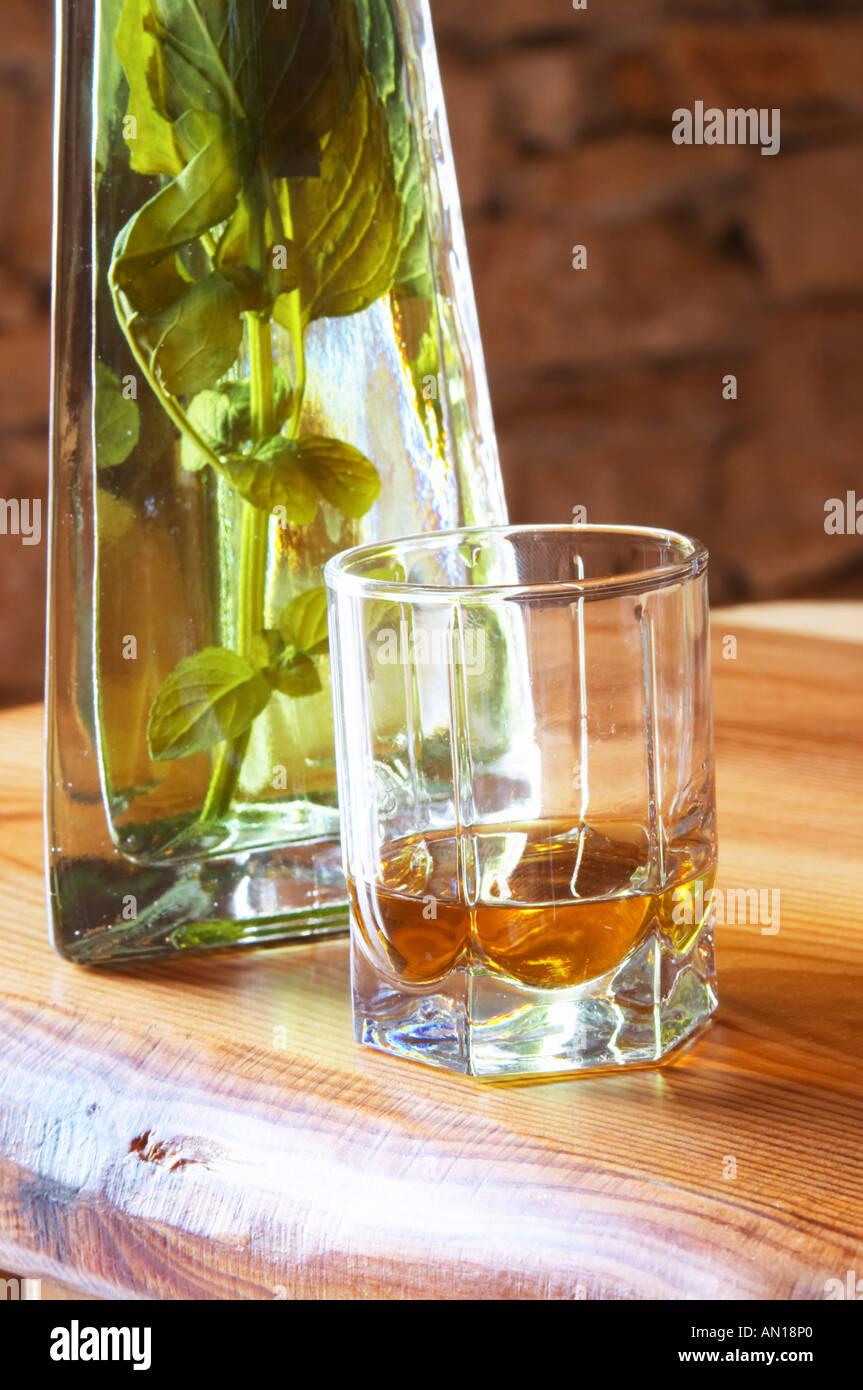 Rakija grappa type spirit flavoured with herbs backlit, Travarica, Toreta Vinarija. Detail with glass and herbs Stock Photo