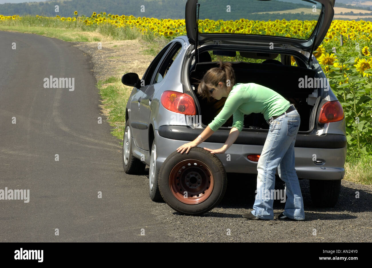 Woman changing her flat tyre - Stock Image