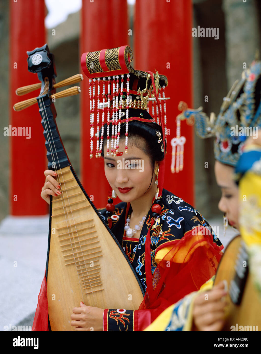 Women Dressed in Traditional Costume Playing  Three Stringed Lute, Beijing, China - Stock Image