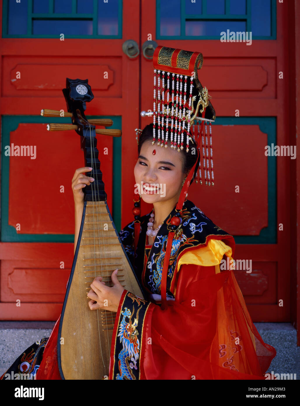 Women Dressed in Traditional Costume Playing Three String Lute, Beijing, China - Stock Image