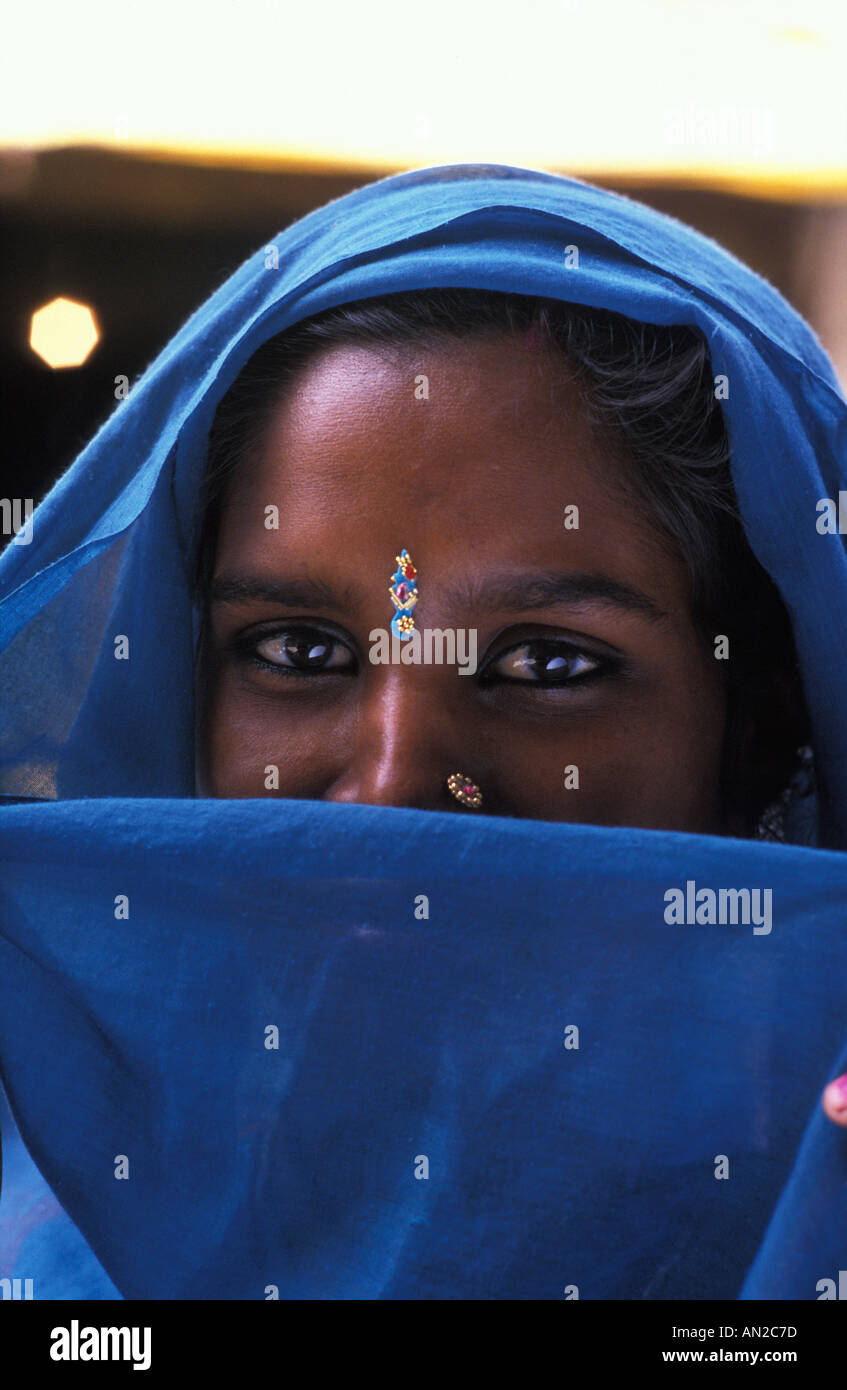 Friendly Hindu woman from Uttar Pradesh with blue headcloth veiling her smile India - Stock Image