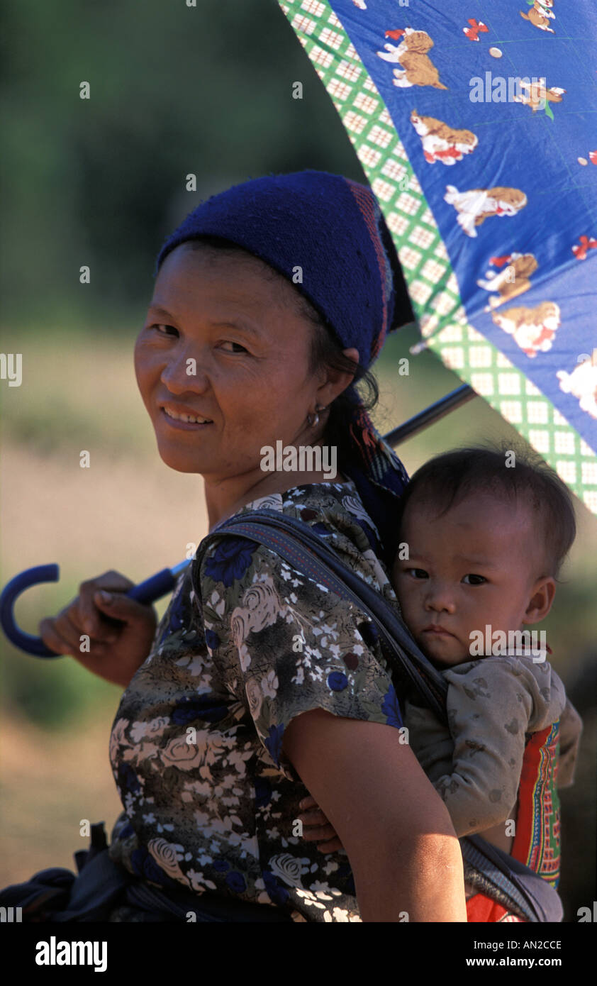 Friendly Lao women with child on back shielded under parasol Vang Vieng Laos - Stock Image