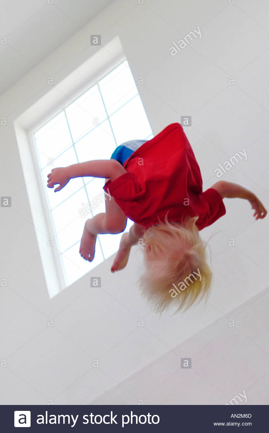 A small little girl thrown in the air - Stock Image