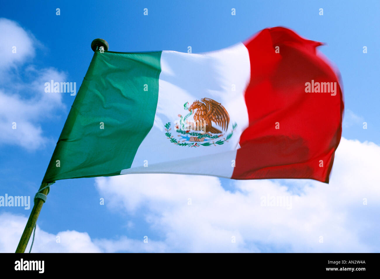 A Mexican flag against a blue sky. - Stock Image
