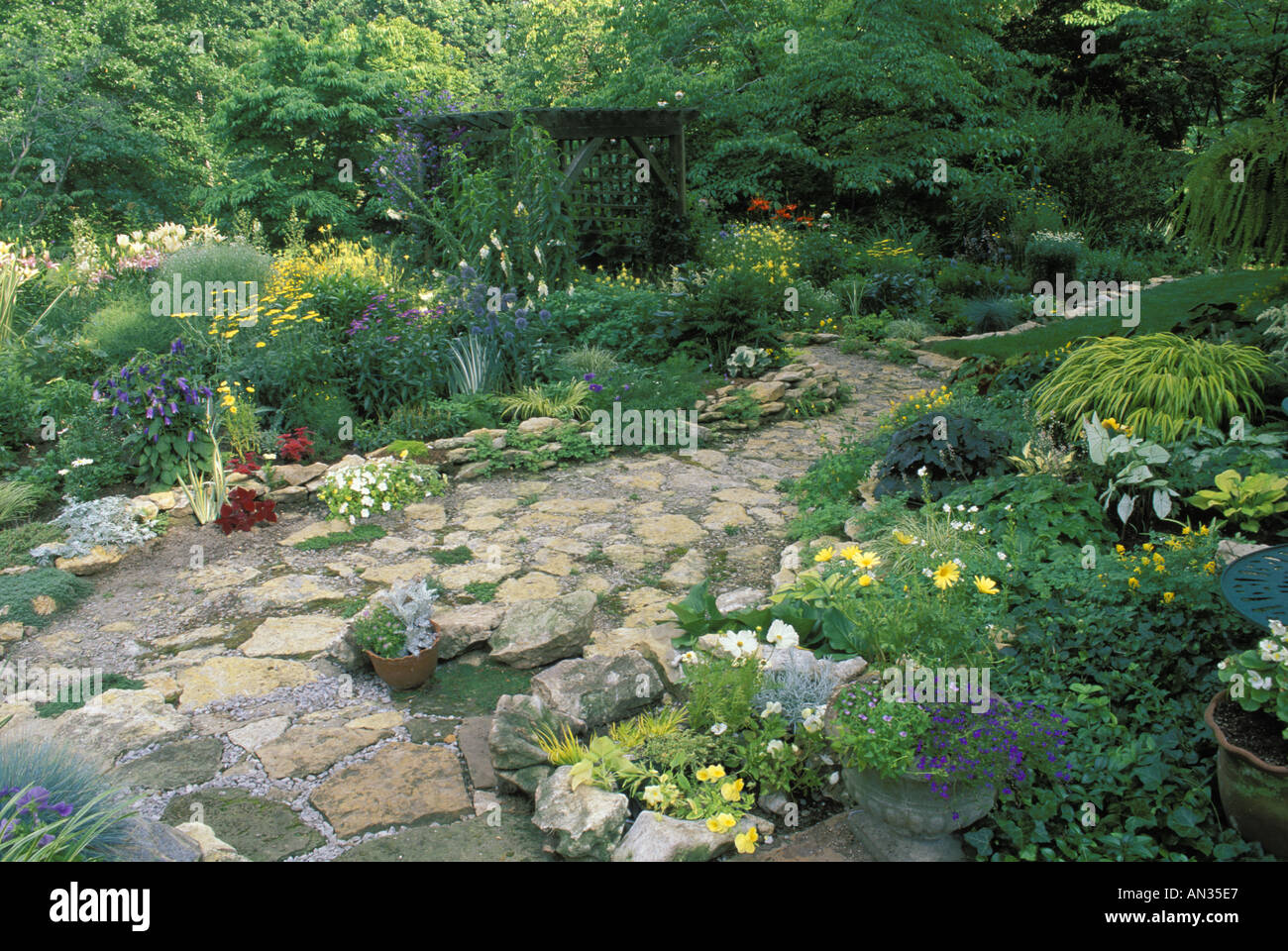 Flagstone Path With Stone Wall In Flower Garden Leads Through Wood Arbor  With Seat Missouri USA