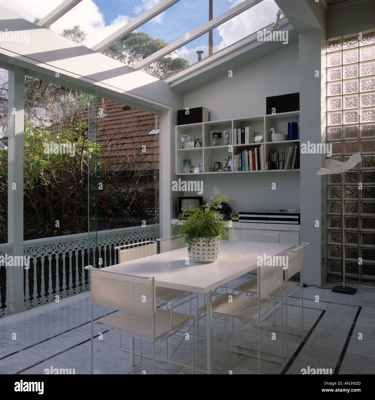 White Table And Chairs In Modern Dining Room Extension With Glass Roof Walls Small Television On Shelving