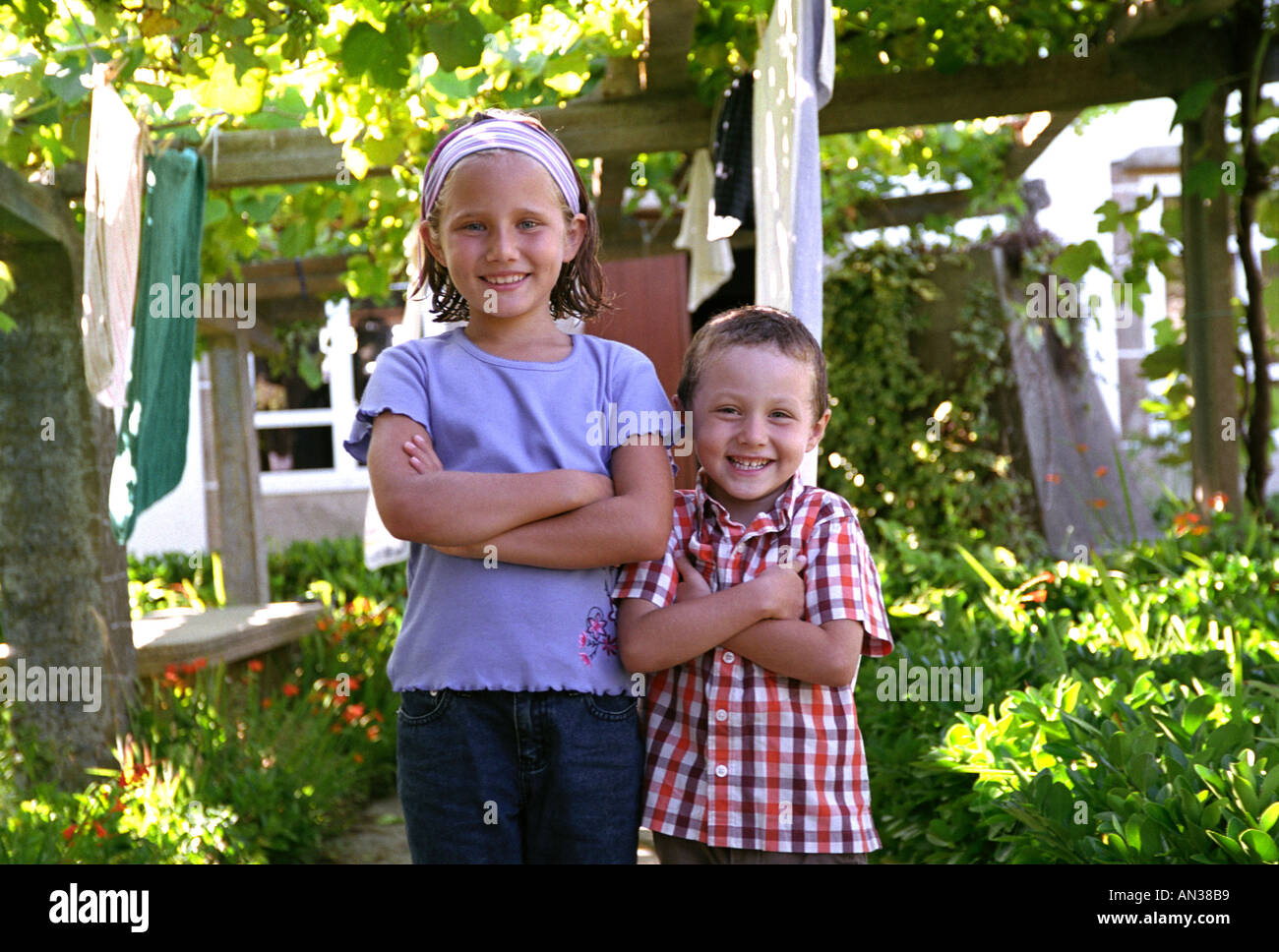Brother and sister posing in the garden - Stock Image
