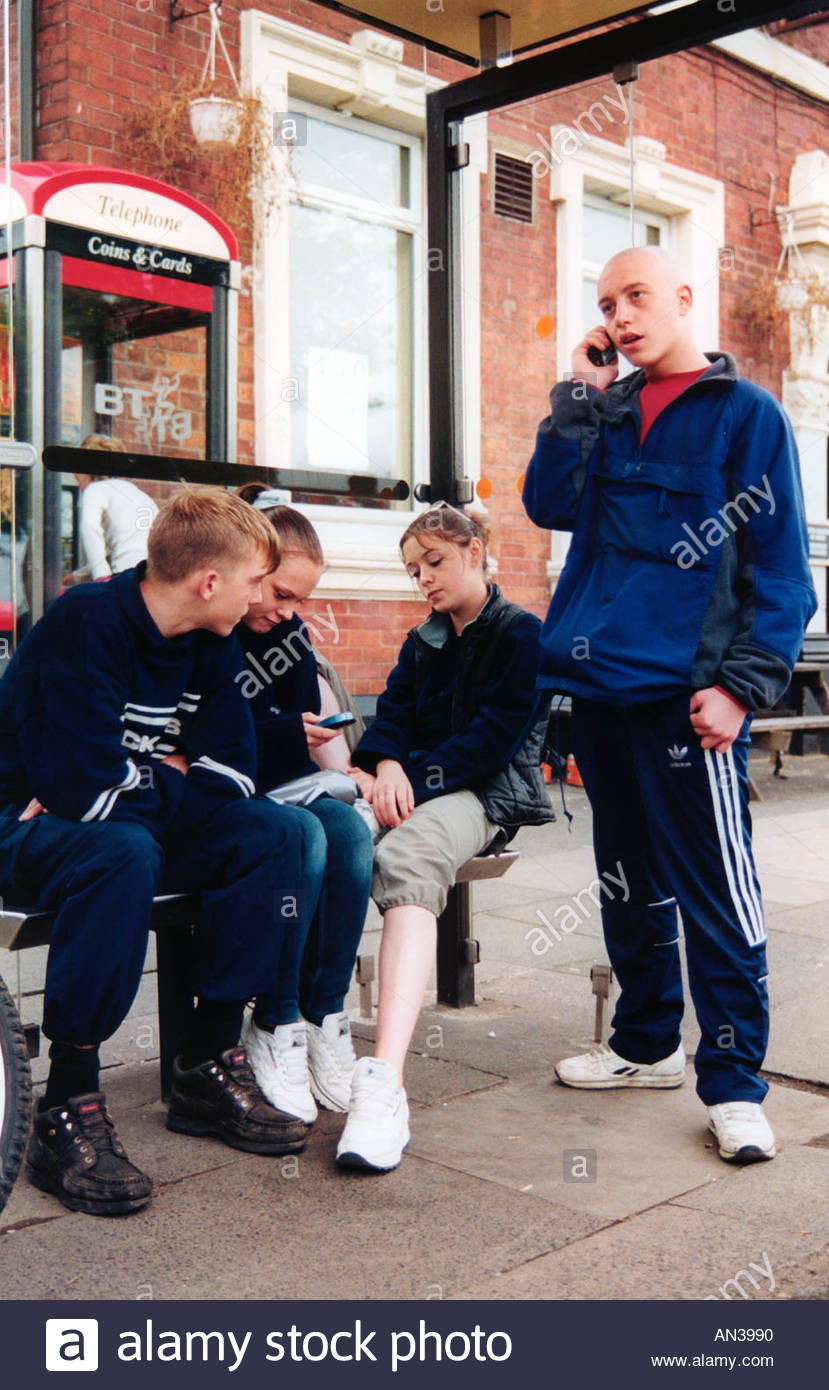 Group of teenagers hanging about at bus stop texting and talking on their mobile phones UK - Stock Image