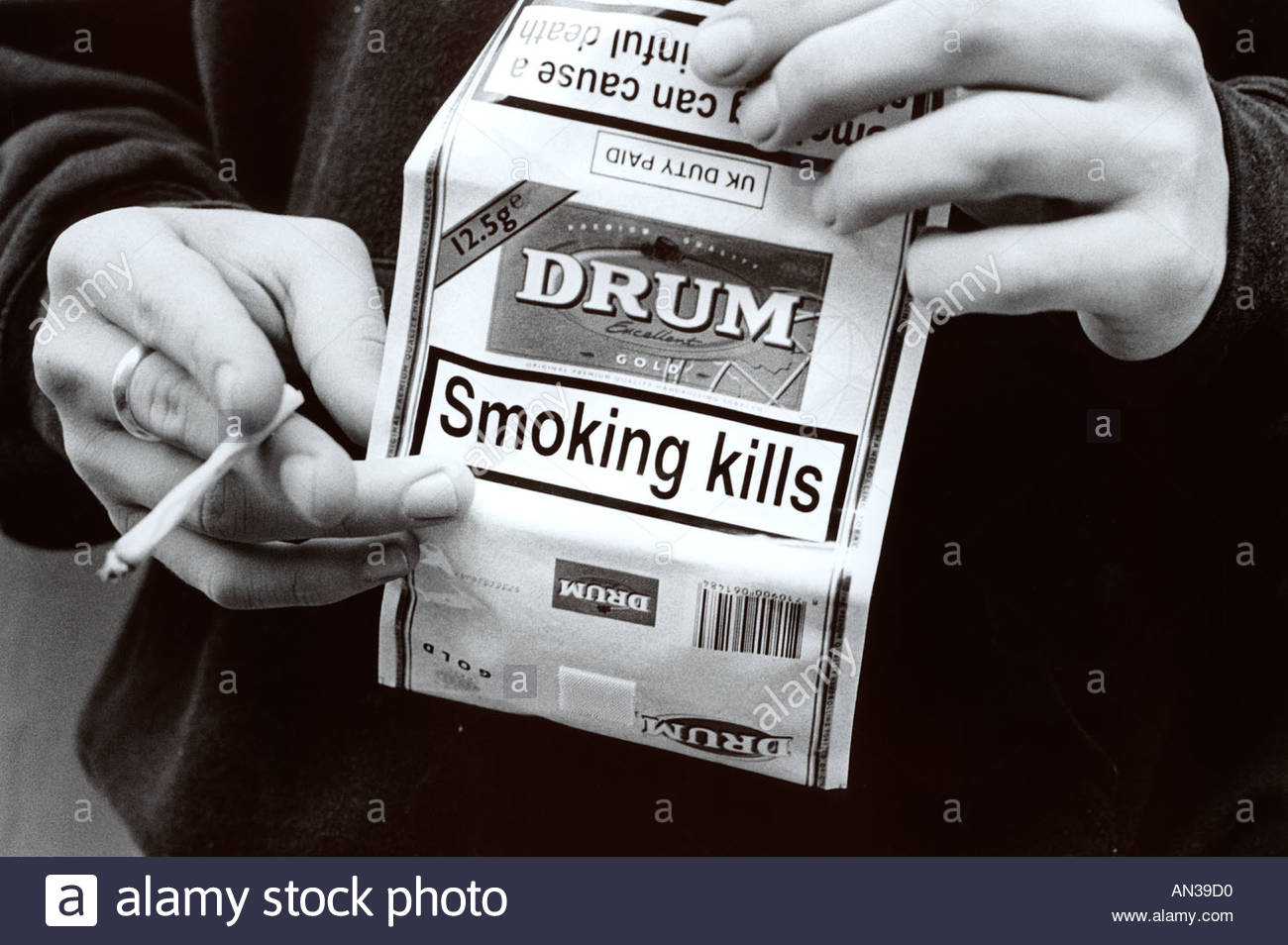 Young man holding packet of Drum roll tobacco and smoking roll up cigarette UK - Stock Image