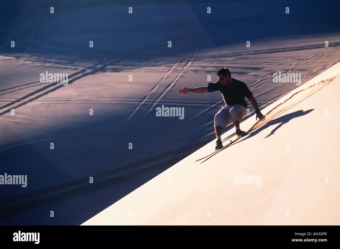 Sandboarding on a sand dune - Stock Image