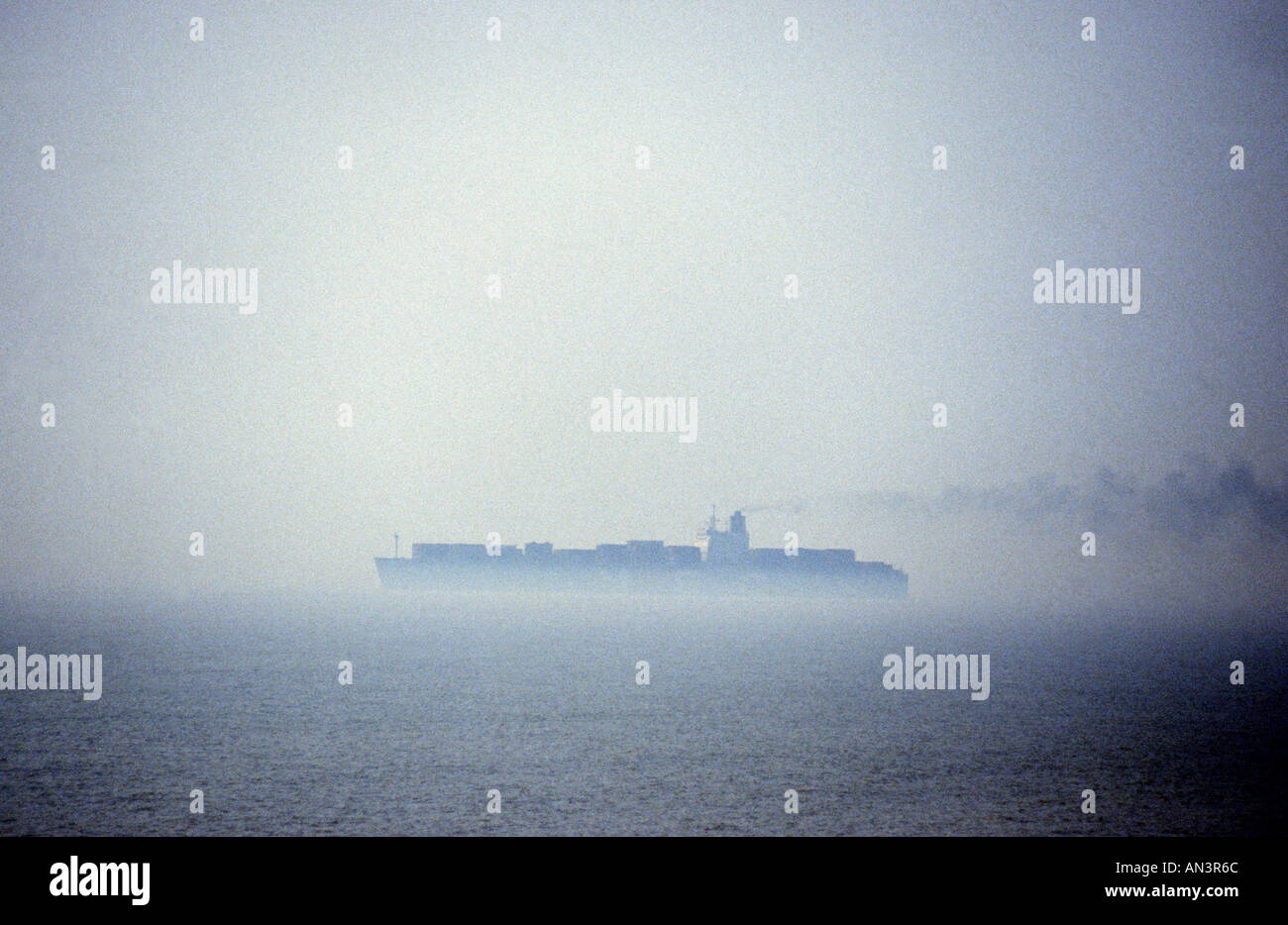 Container ship in fog leaving the Port of Felixstowe, Suffolk, UK. - Stock Image