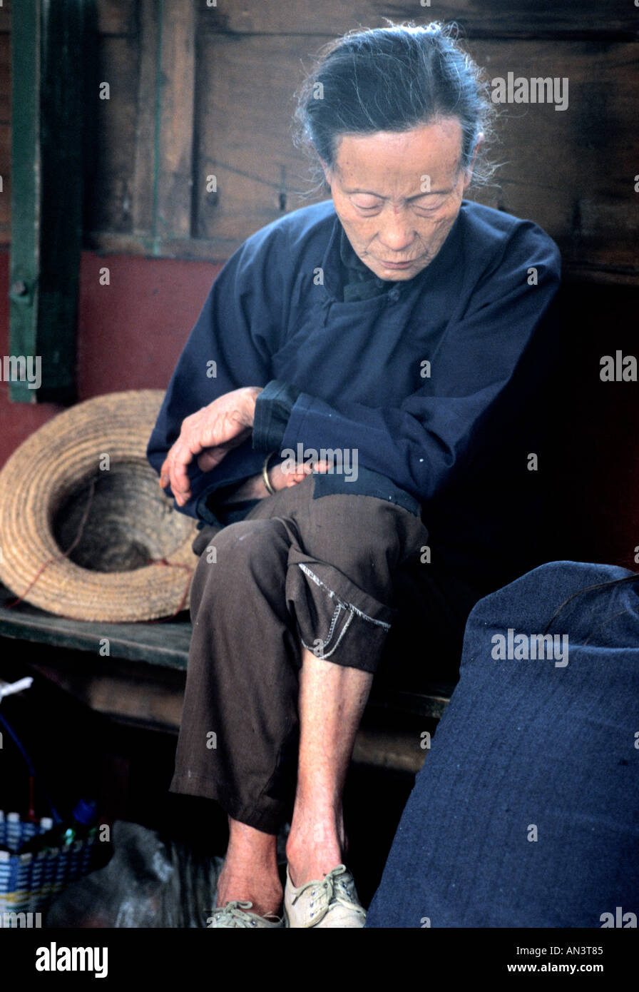 Old Chinese peasant woman in plain blue and brown clothes asleep on a ferry on the Li River near Fuli China - Stock Image