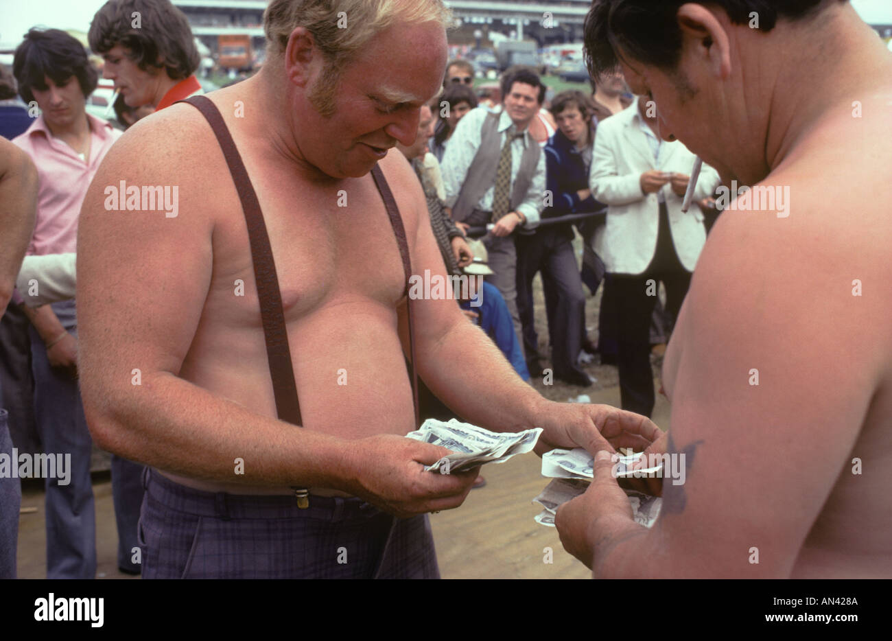Tax free undeclared earnings gambling money changing hands cash hand wads of notes at the Derby horse races HOMER SYKES - Stock Image