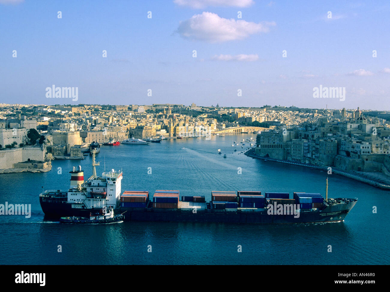 Large cargo ship sails into Valletta harbour / port, Malta - with a pilot boat / tug in the afternoon light - Stock Image