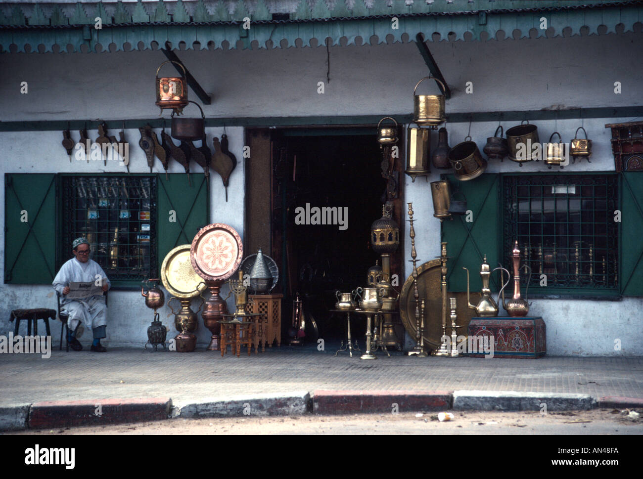 Man reading paper outside metalwork shop Rabat Morocco North Africa - Stock Image