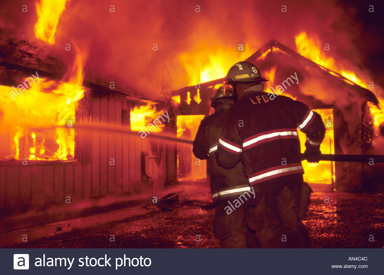 Firefighters attack a spectacular nighttime house fire using a hose line. - Stock Image