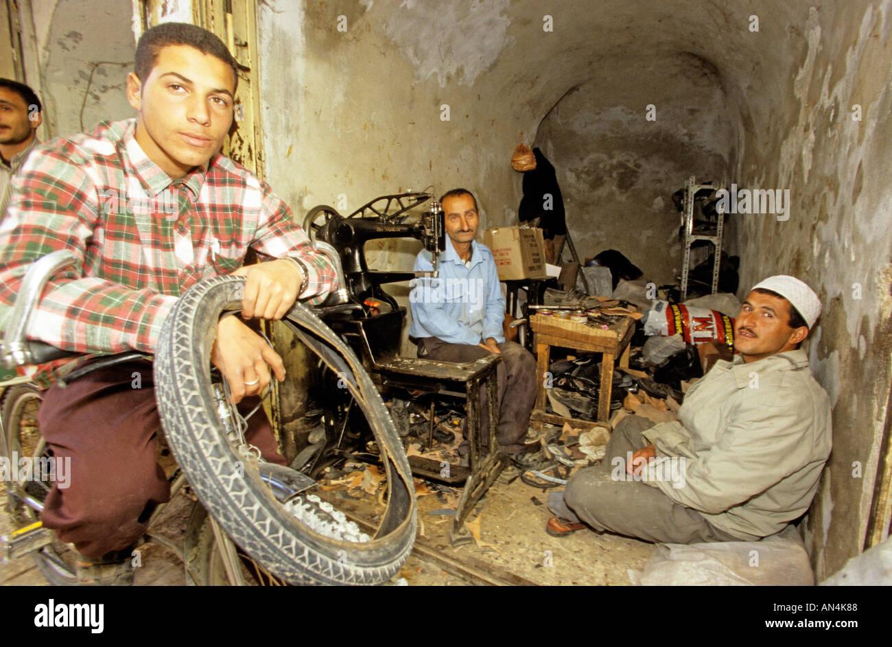 Tyre repairmen in workshop, Hebron, West Bank, Jerusalem Stock Photo
