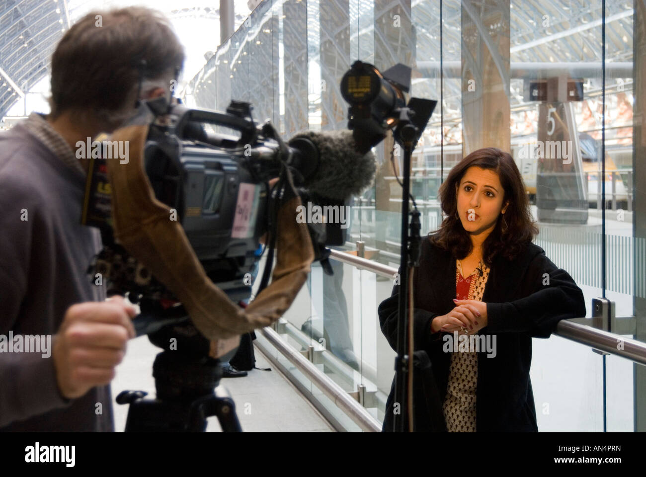 Television news reporter in front of TV camera London England UK - Stock Image