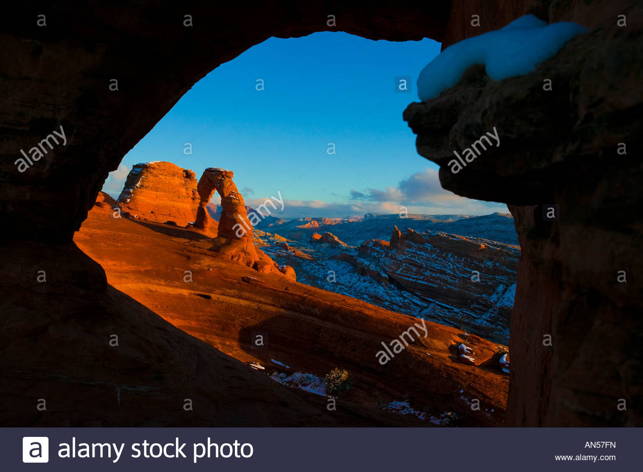 Delicate Arch, dusted by winter snow, is framed by a natural arch at sunset in Arches National Park near Moab, Utah. Stock Photo