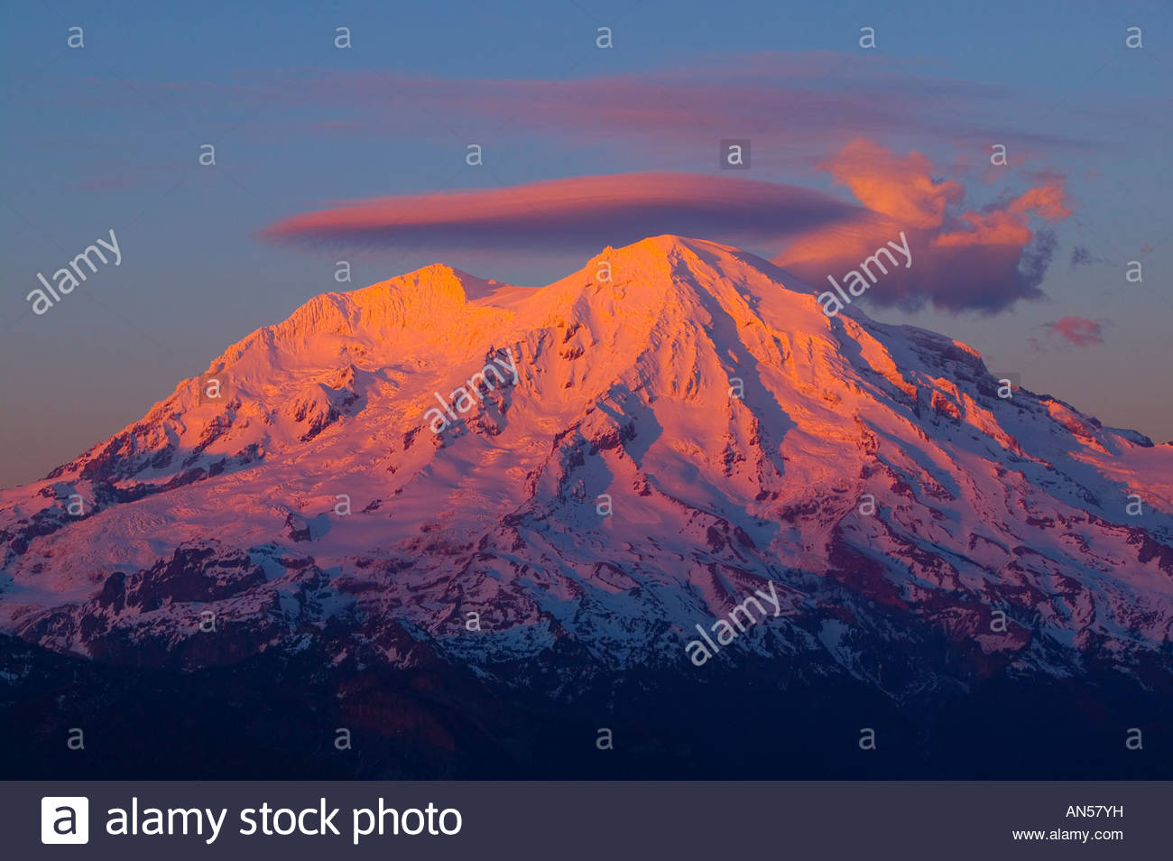 The last light of day illuminates the winter snow pack on Mount Rainier in this view from High Rock. - Stock Image