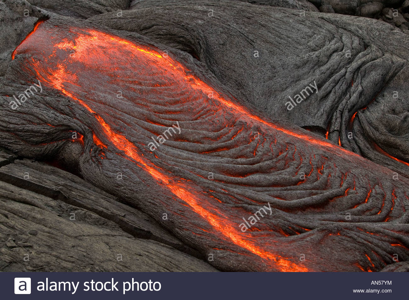 Molten pahoehoe lava flows at the end of a lava tube from the Pu`u O`o Kila vent in Volcanoes National Park on Hawaii. - Stock Image