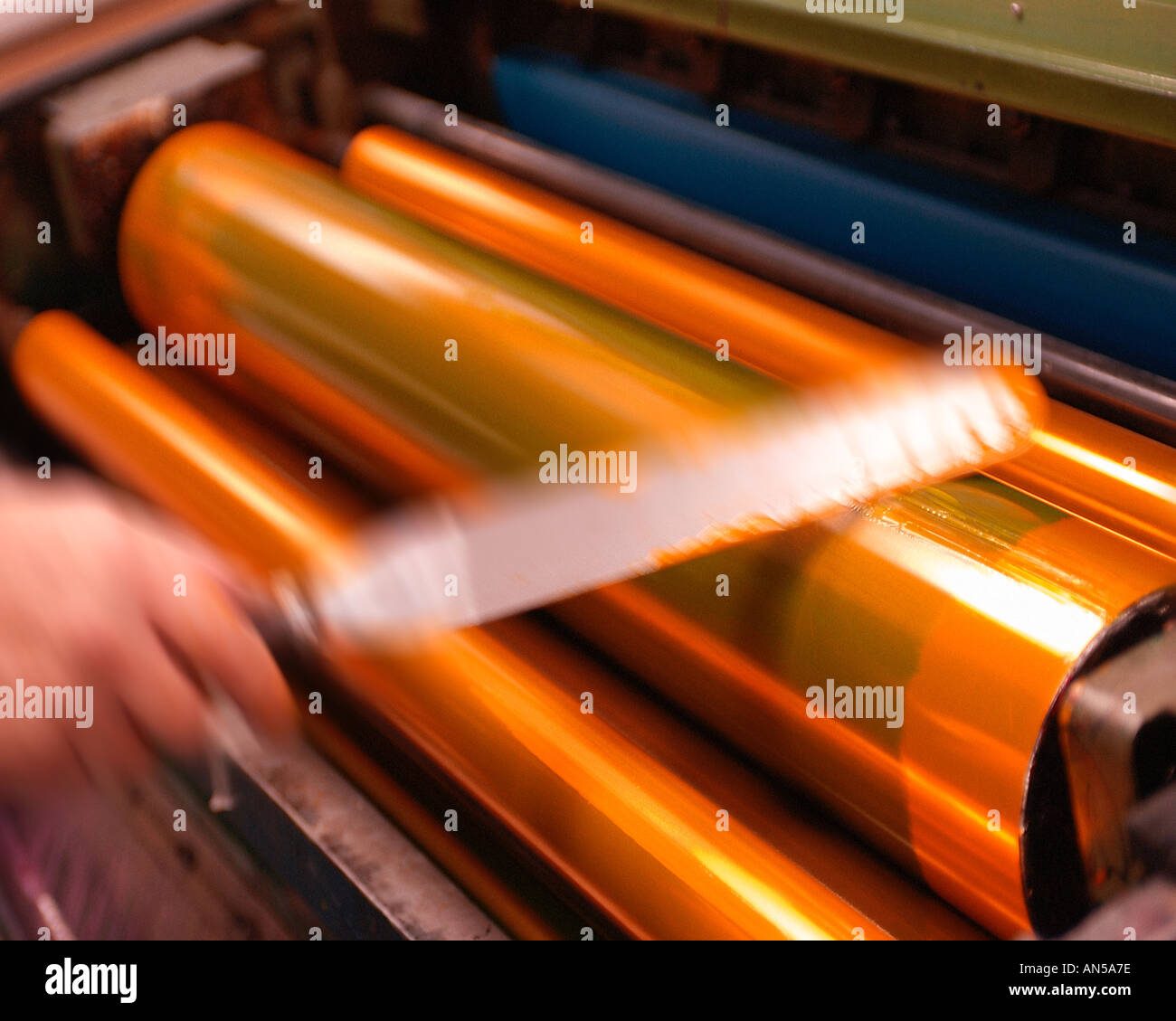 PRINTER APPLYING INK TO ROLLERS OF PRINTING PRESS - Stock Image