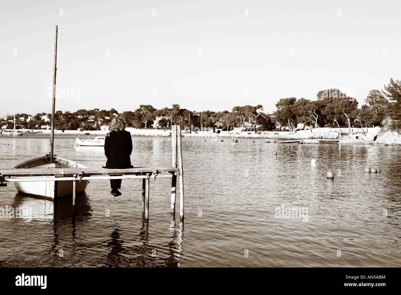 A person sitting on a pier in Antibes France Sepia tone Copy space - Stock Image