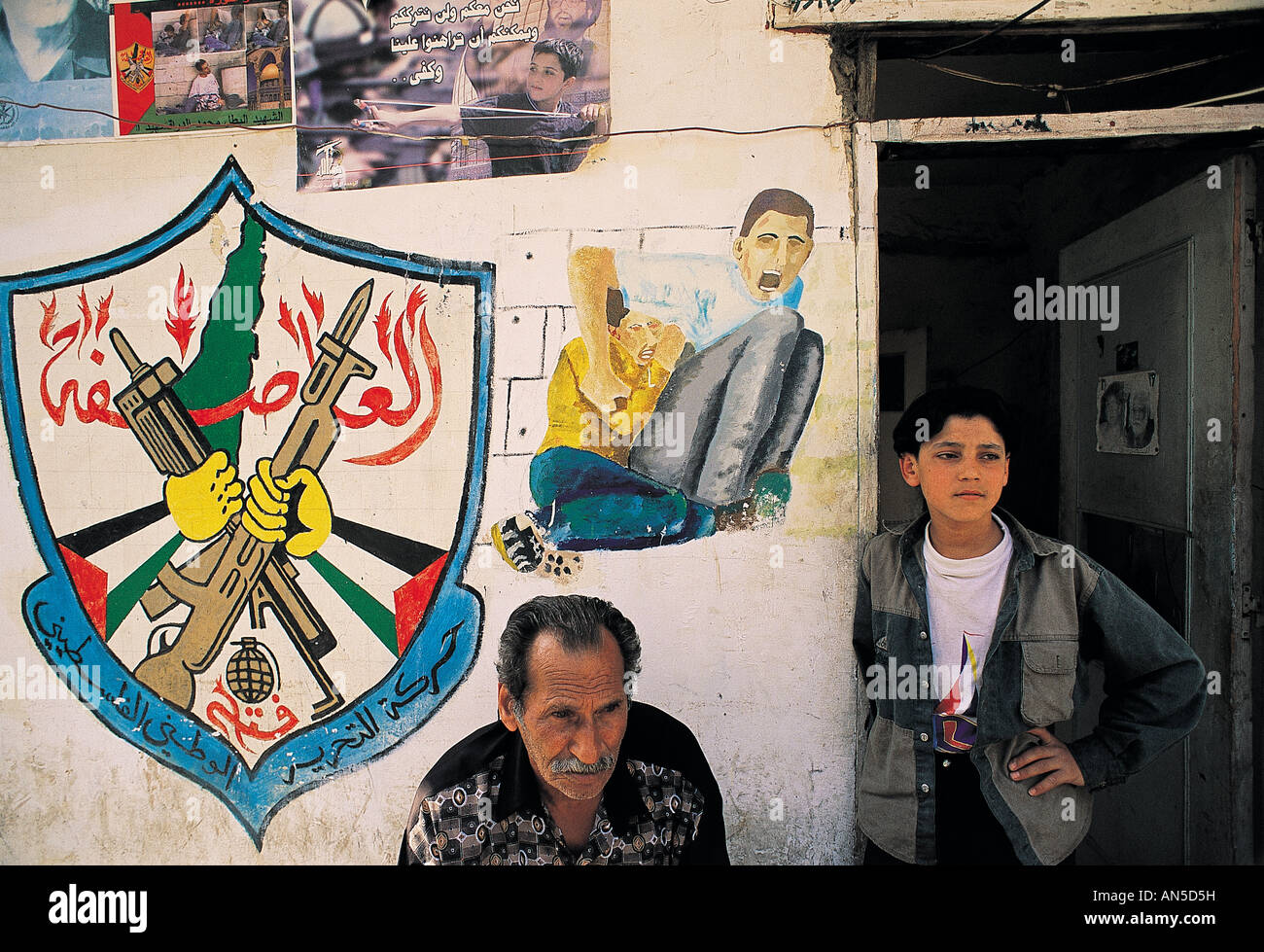 Palestinians living in Beirut with intifada paintings on the walls . - Stock Image