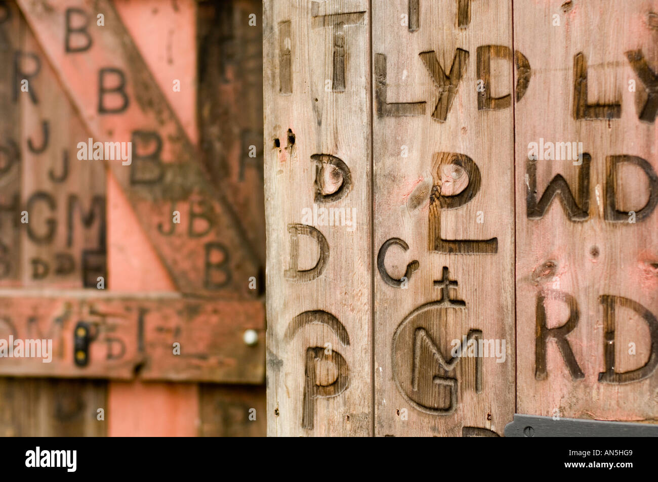wooden shutters on old blacksmith's shop Penybont Powys wales, with branded marks of letters and symbols scorched into the doors - Stock Image