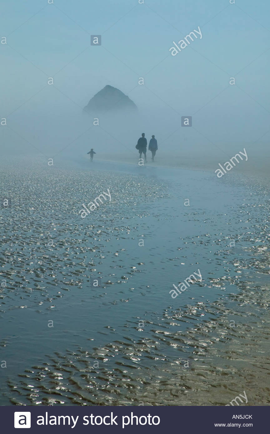 A young family walks on the beach near Haystack Rock, Oregon in thick fog. - Stock Image