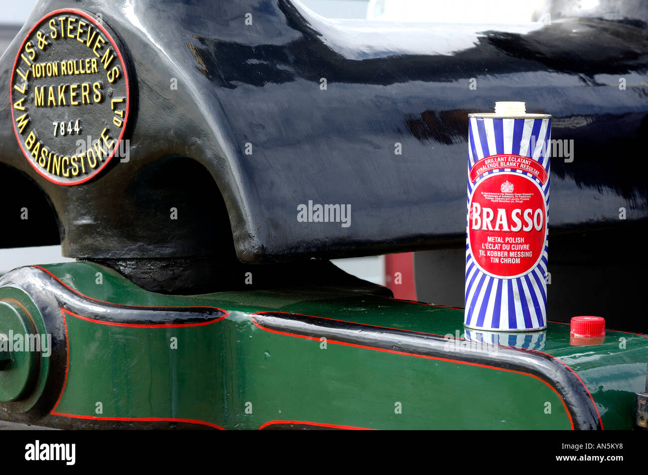 Can of brasso metal polish stood on front of vintage steam engine showing highly polished ironwork - Stock Image